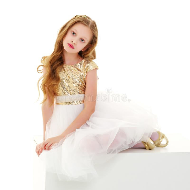 Lilla flickan sitter p? ett vitt baner royaltyfri fotografi