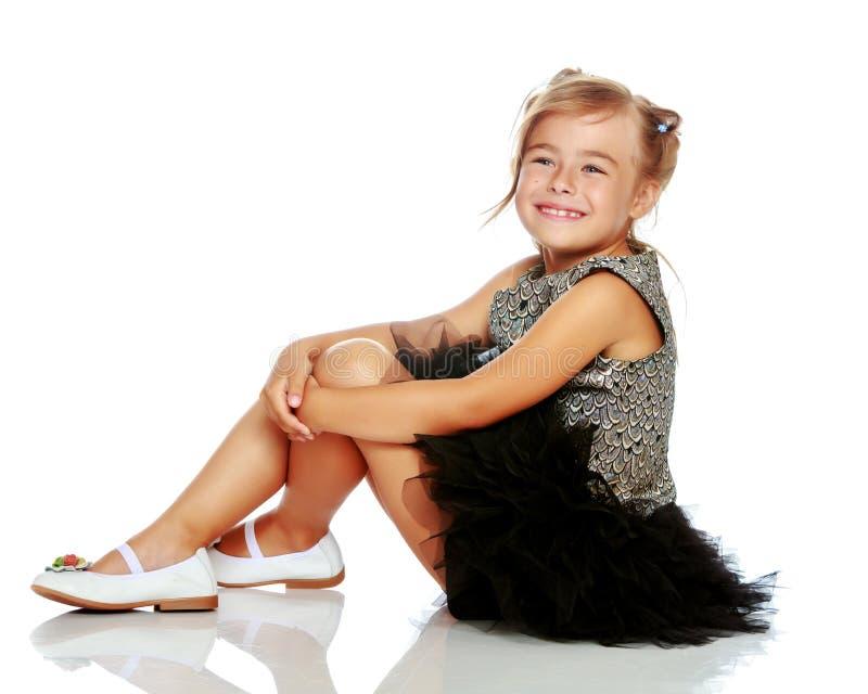 Lilla flickan sitter p? golvet royaltyfria bilder
