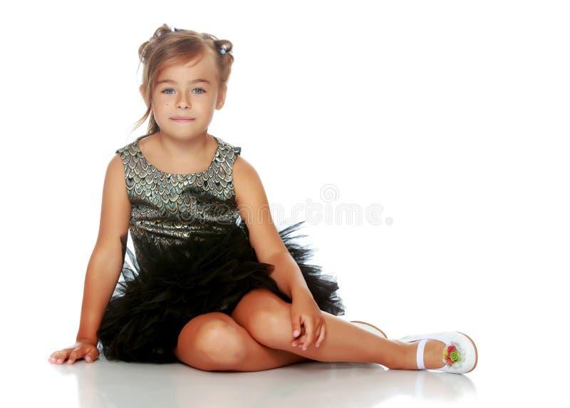 Lilla flickan sitter p? golvet arkivbilder