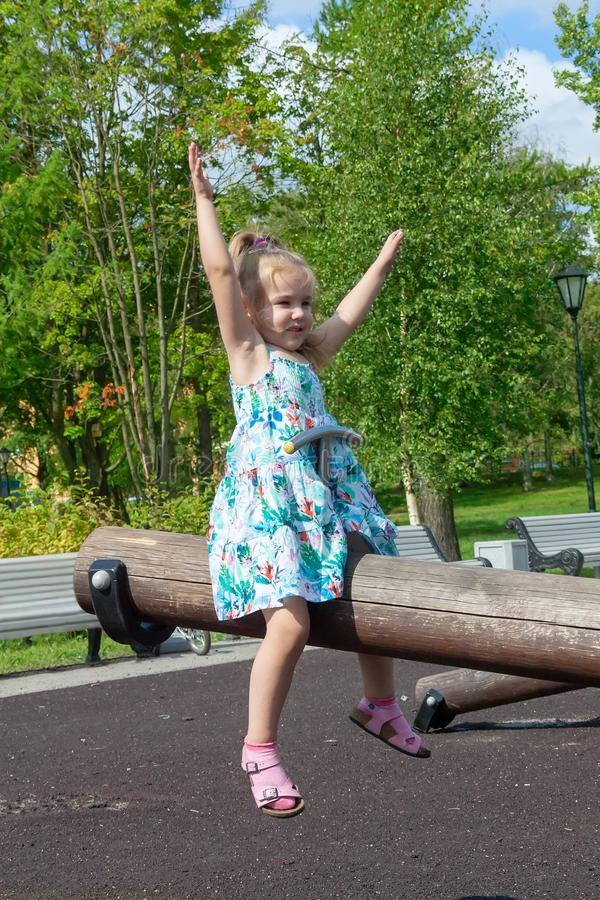 Lilla flickan skakar på en gunga i parkera royaltyfri bild
