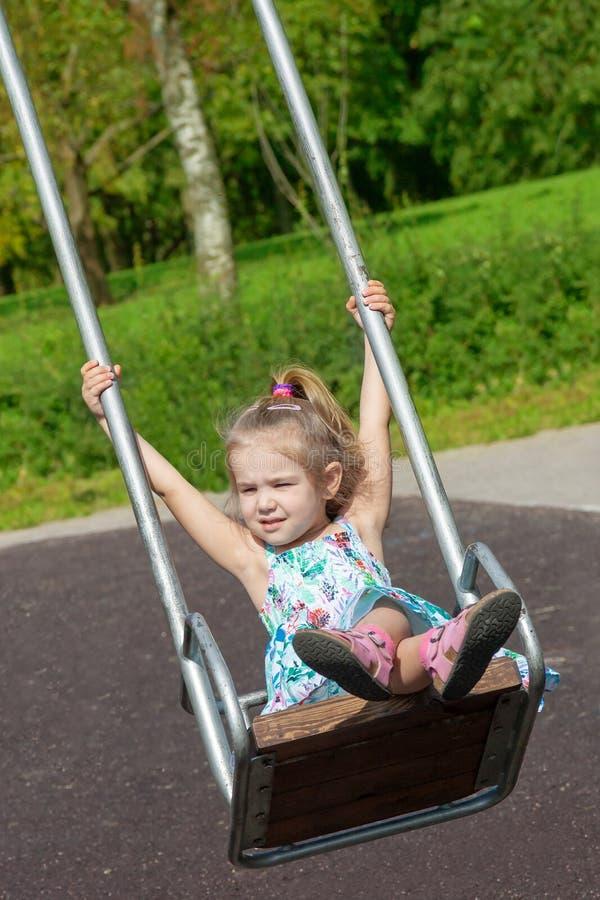 Lilla flickan skakar på en gunga i parkera arkivbilder