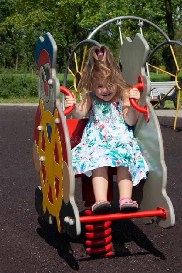 Lilla flickan skakar på en gunga i parkera royaltyfria foton