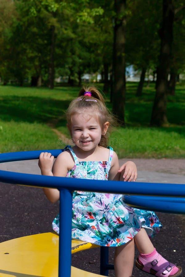 Lilla flickan skakar på en gunga i parkera fotografering för bildbyråer