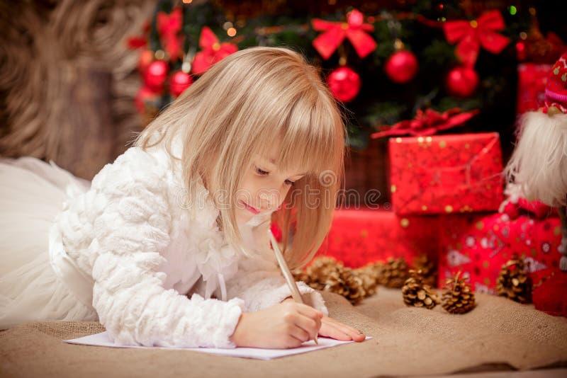 Lilla flickan skrivar ett brev till Santa Claus royaltyfria foton