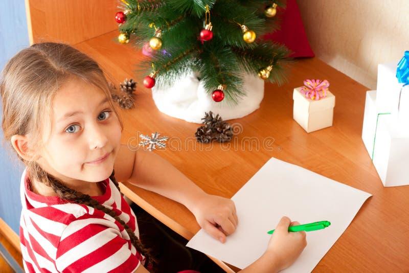 Lilla flickan skrivar ett brev till Santa Claus på vitbok royaltyfri bild