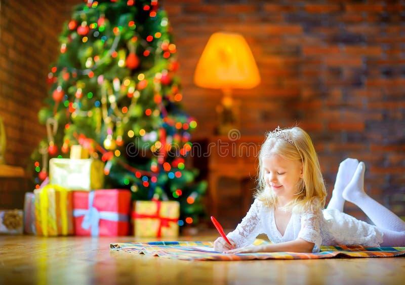 Lilla flickan skrivar ett brev till santa som ligger på golvet nära julgranen royaltyfria foton