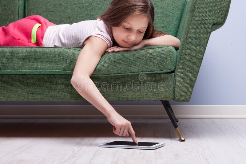 Lilla flickan som använder en minnestavla, kopplade av på en soffa arkivfoton
