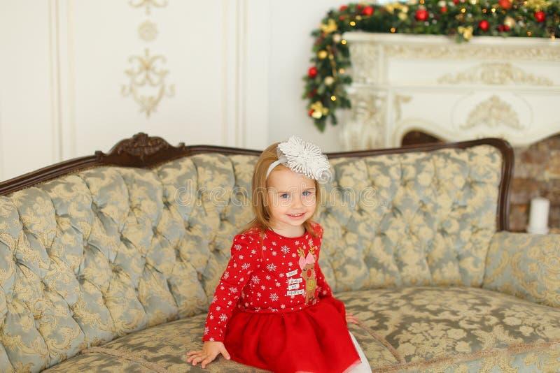 Lilla flickan som bär rött klänningsammanträde på soffan nära, dekorerade spisen royaltyfria bilder