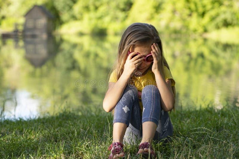 Lilla flickan som bara sitter och tänker om något, flickan, är ledsen på flodbanken, på en solig varm sommardag royaltyfri foto