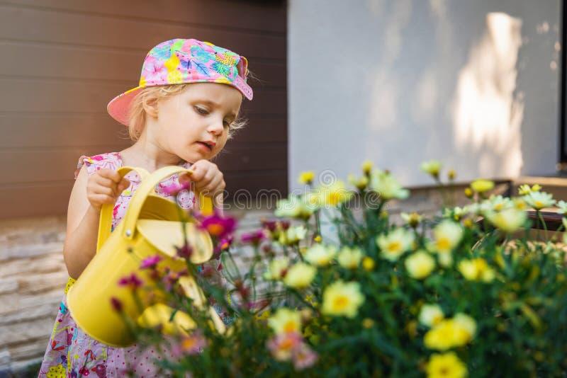 Lilla flickan som bevattnar blommor med gult bevattna kan arkivfoton