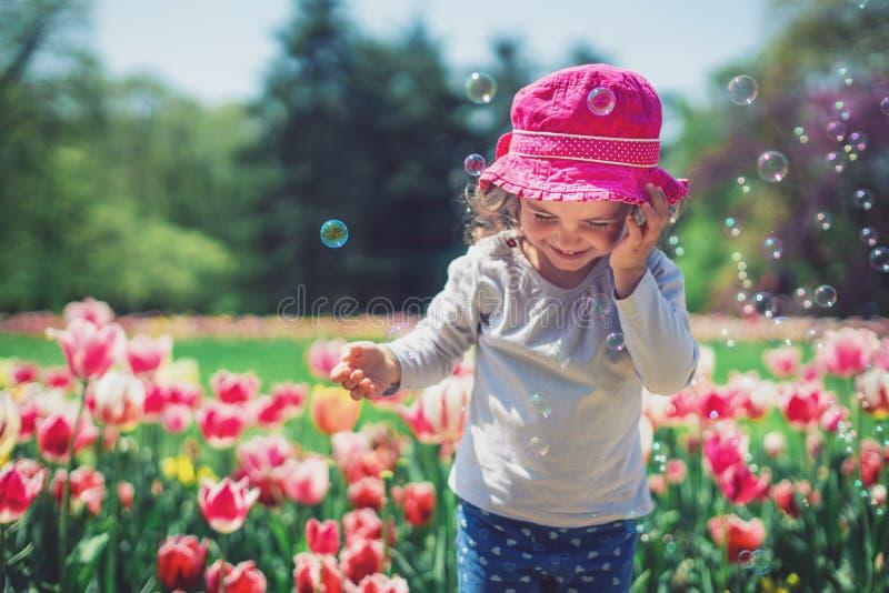 Lilla flickan som blåser såpbubblor i sommar, parkerar och blommande tulpan arkivbild