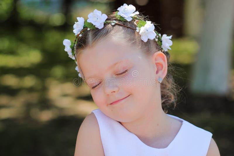Lilla flickan som drömmer med ögon, stängde sig, barnet med en krans av konstgjorda blommor på hennes huvud royaltyfri foto