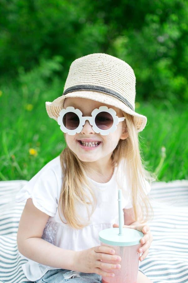 Lilla flickan som dricker den läckra jordgubbesmoothien med, mjölkar och glass arkivbild