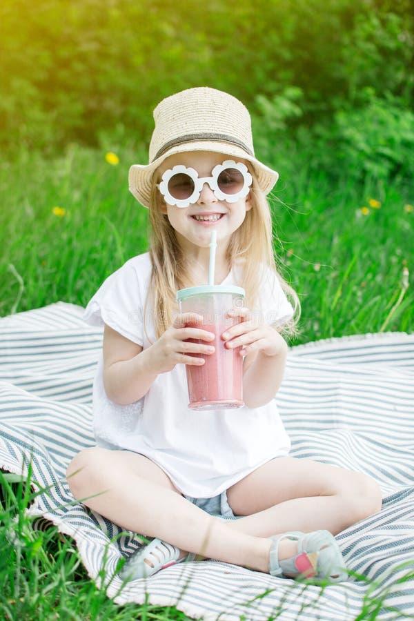Lilla flickan som dricker den l?ckra jordgubbesmoothien med, mj?lkar och glass arkivfoto
