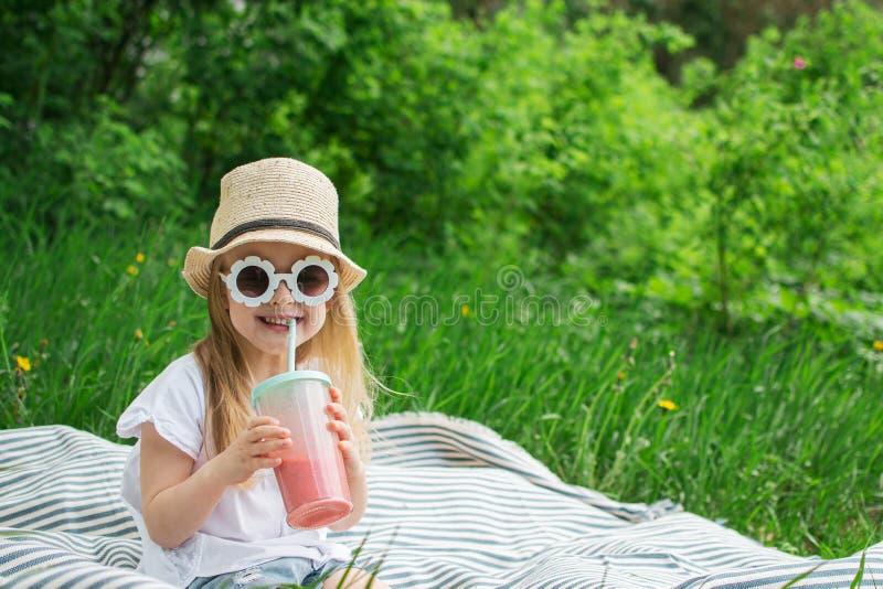 Lilla flickan som dricker den l?ckra jordgubbesmoothien med, mj?lkar och glass arkivbilder
