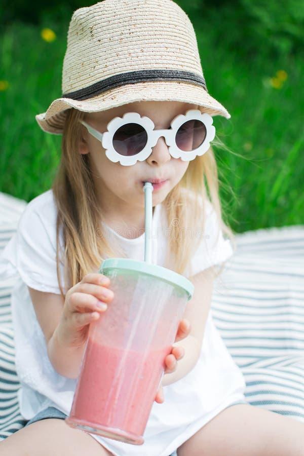 Lilla flickan som dricker den l?ckra jordgubbesmoothien med, mj?lkar och glass royaltyfri bild