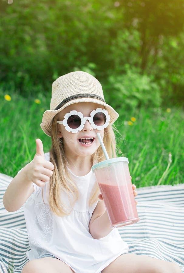 Lilla flickan som dricker den l?ckra jordgubbesmoothien med, mj?lkar och glass royaltyfria foton