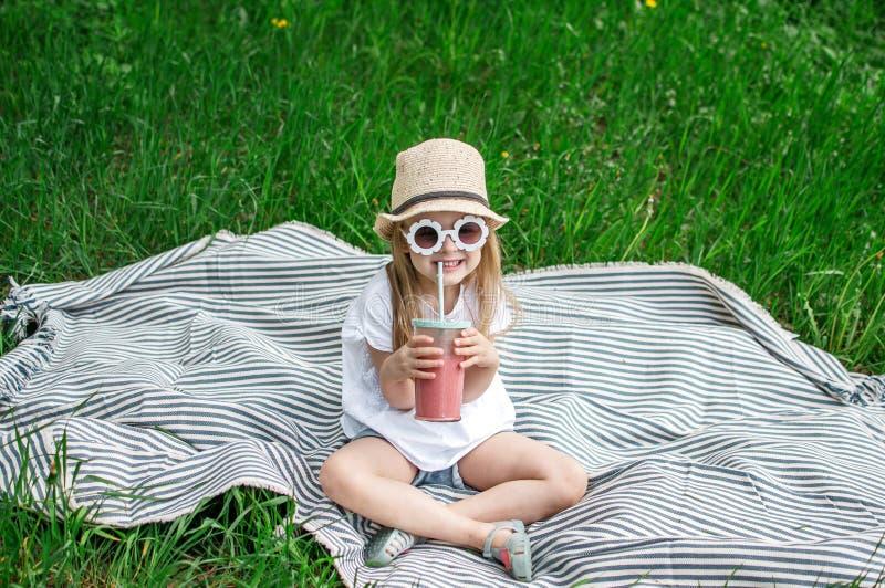 Lilla flickan som dricker den l?ckra jordgubbesmoothien med, mj?lkar och glass royaltyfria bilder