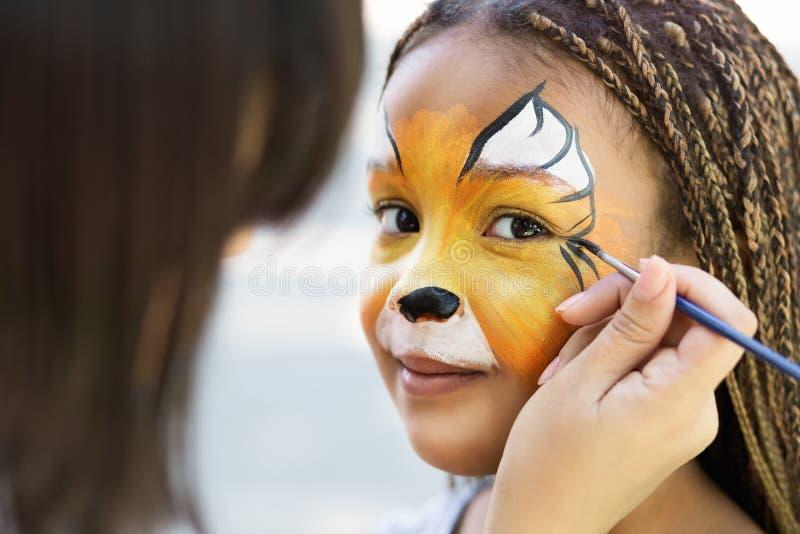 Lilla flickan som får hennes framsida, målade vid framsidamålningkonstnären arkivbilder