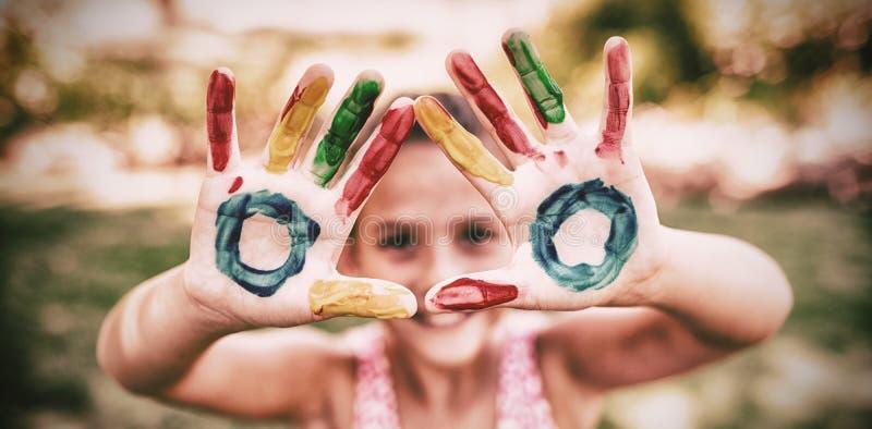Lilla flickan som gör en triangel med henne, målade händer till kameran royaltyfria bilder