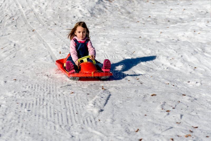 Lilla flickan som glider med, guppar i den insnöade vintertiden royaltyfria foton