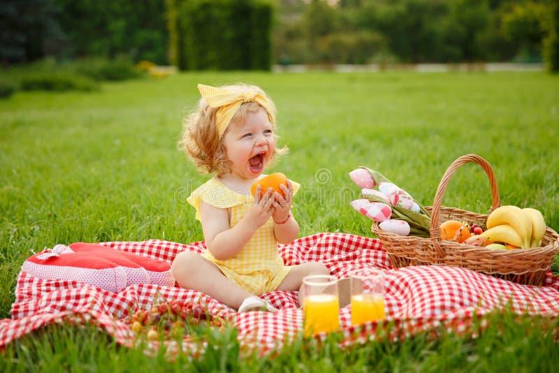 Lilla flickan som har lunch parkerar in fotografering för bildbyråer