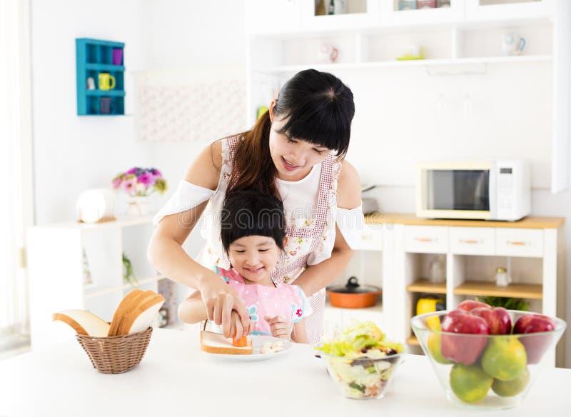 Lilla flickan som hjälper hennes moder, förbereder mat i köket royaltyfri foto