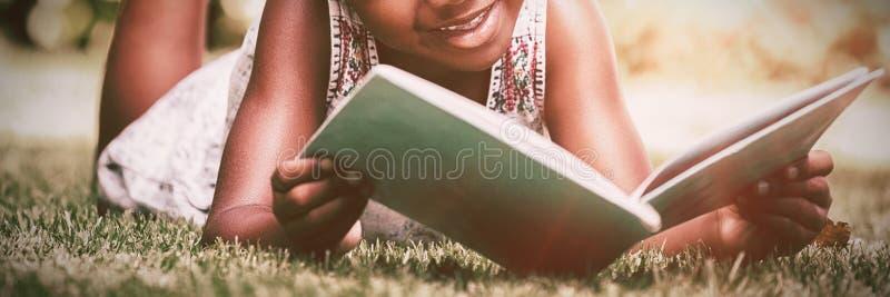 Lilla flickan som läser en bok på, parkerar arkivbild