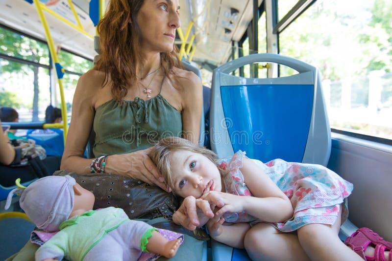 Lilla flickan som ligger på moder, lägger benen på ryggen på bussen fotografering för bildbyråer