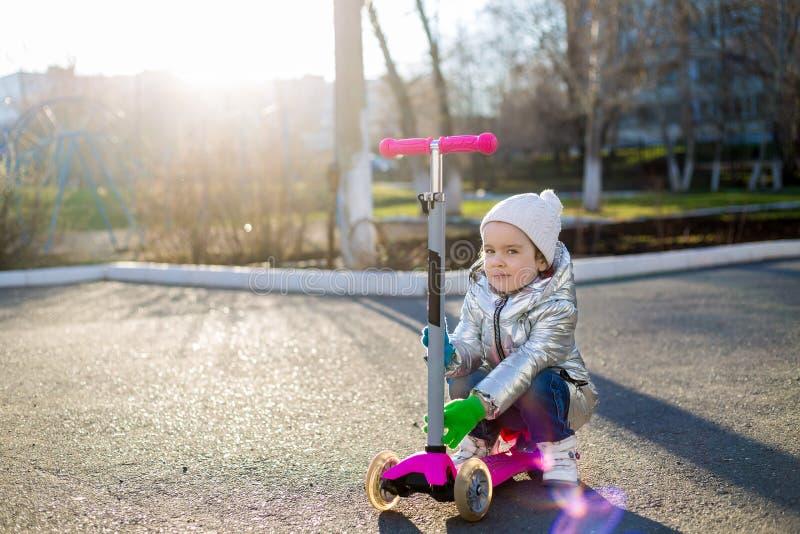Lilla flickan som rider en sparkcykel i, parkerar p? en solig v?rdag Aktiv fritid och utomhus- sport f?r barn royaltyfri foto