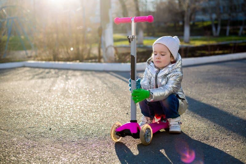 Lilla flickan som rider en sparkcykel i, parkerar p? en solig v?rdag Aktiv fritid och utomhus- sport f?r barn arkivbilder