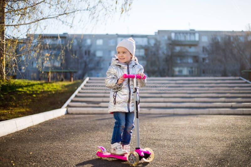 Lilla flickan som rider en sparkcykel i, parkerar p? en solig v?rdag Aktiv fritid och utomhus- sport f?r barn arkivfoto