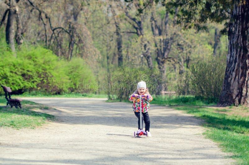 Lilla flickan som rider en sparkcykel parkerar på våren arkivbild