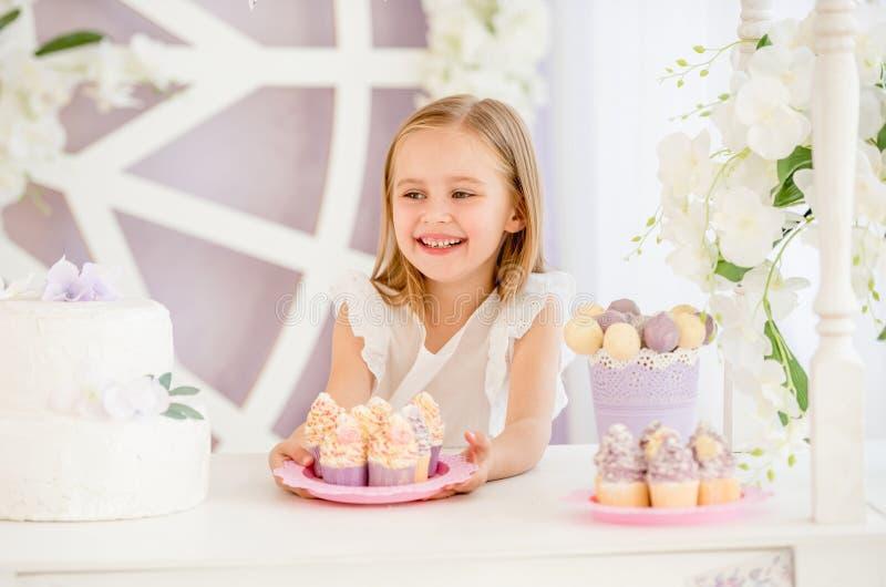 Lilla flickan som rymmer en rosa platta med sötsaken, bakar ihop i godisstången arkivbild