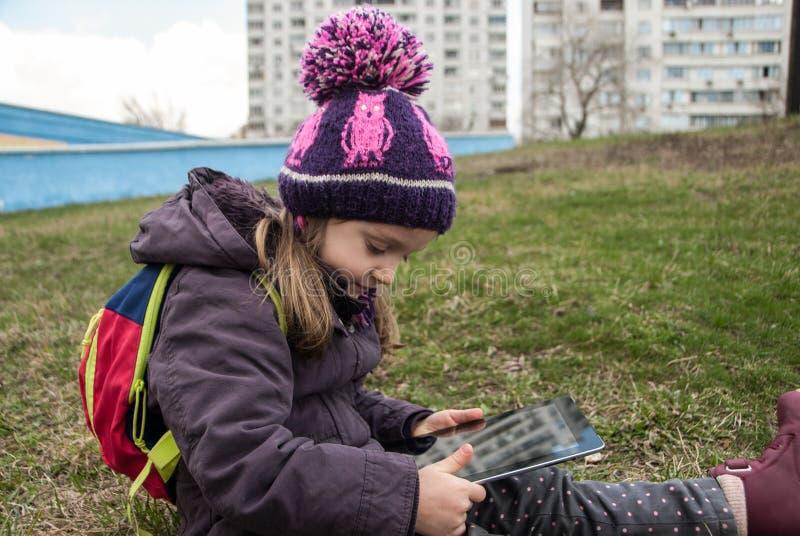 Lilla flickan som sitter på ett gräs i en stad, parkerar den hållande ögonen på smartphonen royaltyfri fotografi