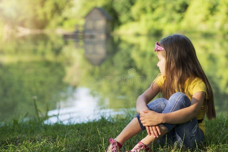 Lilla flickan som sitter på flodbanken, som har täckt hennes framsida med hennes händer, flickan, är ledsen på flodbanken, på ett royaltyfri foto