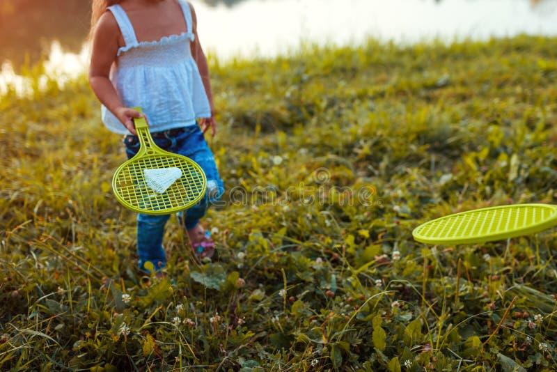 Lilla flickan som spelar badminton med systern i sommar, parkerar Ungar som har roligt utomhus Stäng sig upp av fjäderboll arkivfoto