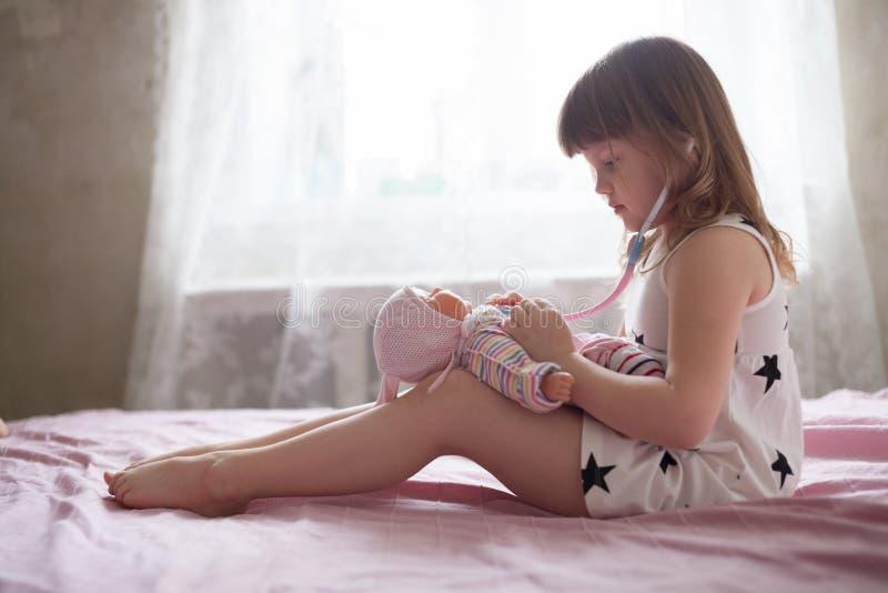 Lilla flickan som spelar doktorn på säng, flicka behandlar dockan, ret royaltyfri fotografi