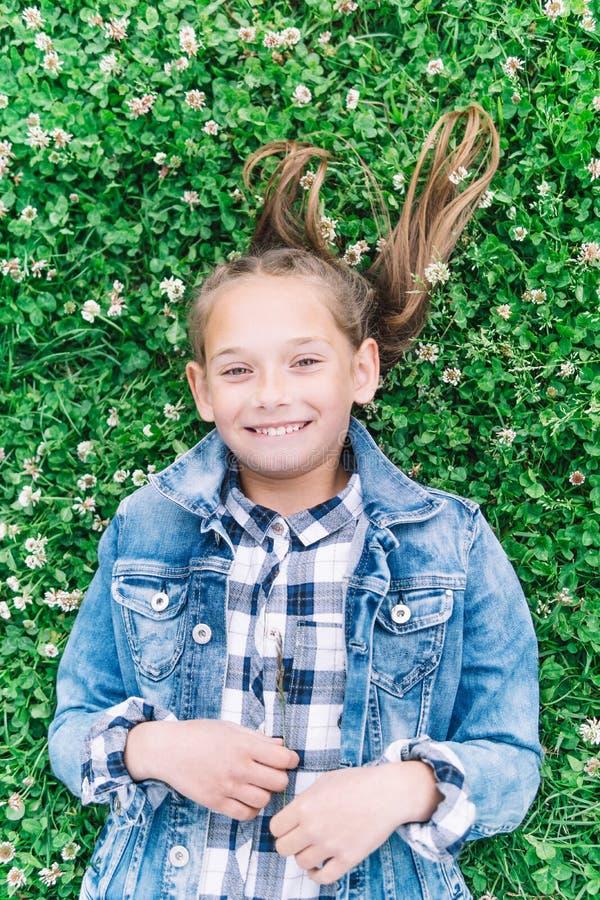 Lilla flickan som spelar i, parkerar i grön bakgrund med blommor arkivfoto