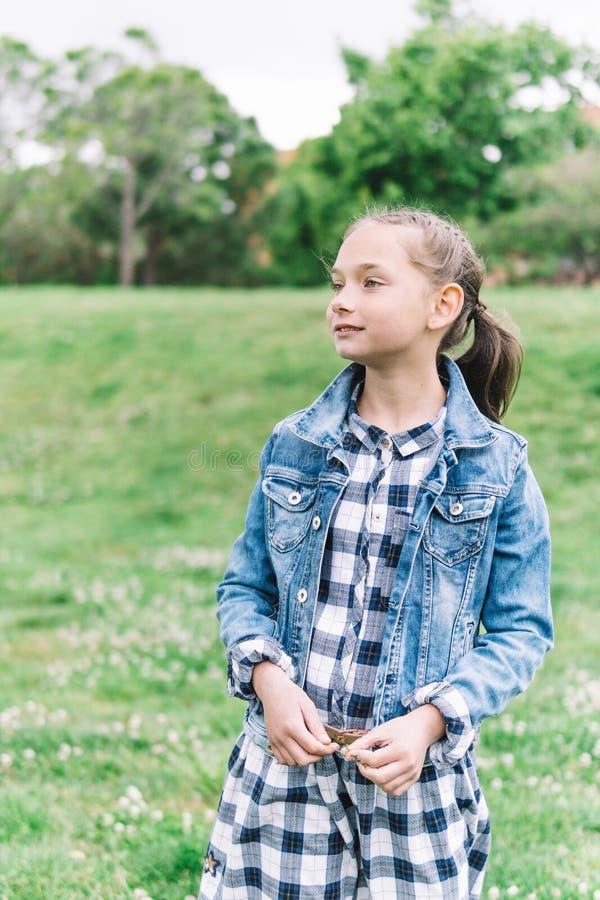 Lilla flickan som spelar i, parkerar i grön bakgrund arkivfoto