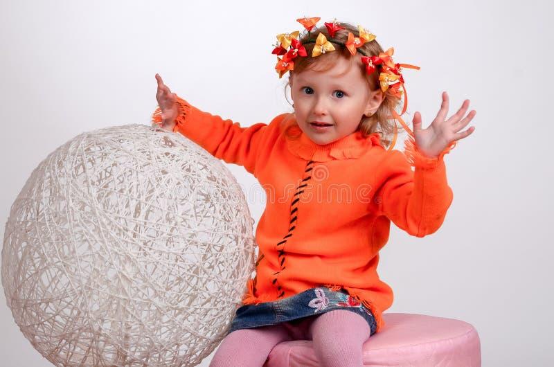 Lilla flickan som spelar med garn, klumpa ihop sig på en vit bakgrund royaltyfri foto