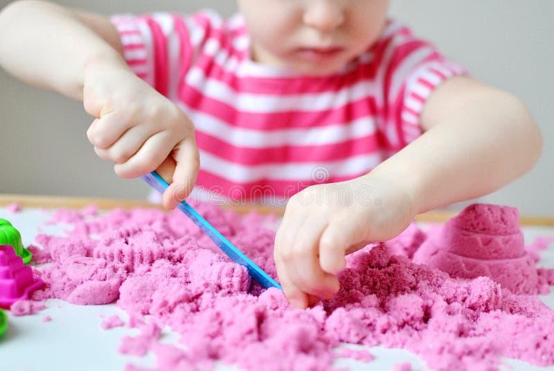Lilla flickan som spelar med hemmastadd tidig utbildning för rosa kinetisk sand som förbereder sig för skolautvecklingsbarn, spel fotografering för bildbyråer