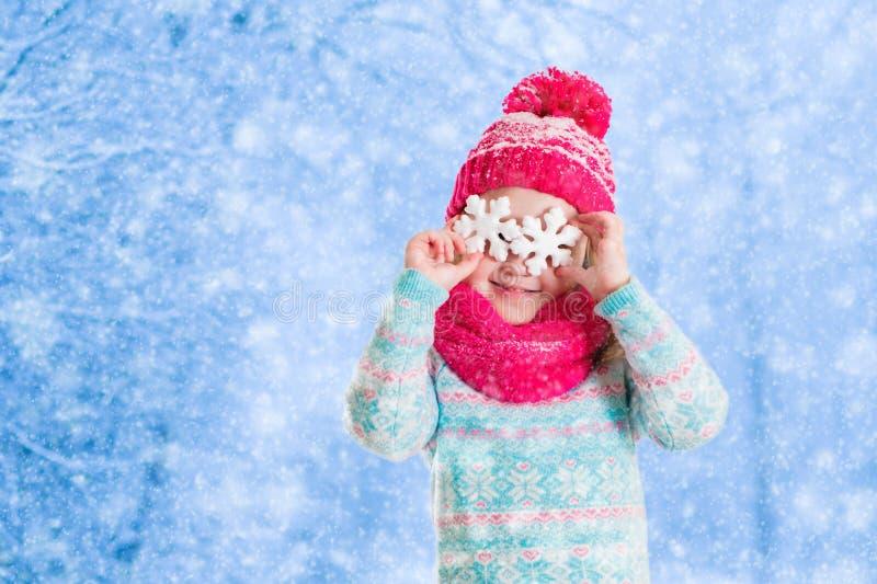 Lilla flickan som spelar med leksaksnö, flagar i vinter parkerar arkivbilder