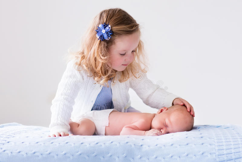 Lilla flickan som spelar med nyfött, behandla som ett barn brodern arkivfoto