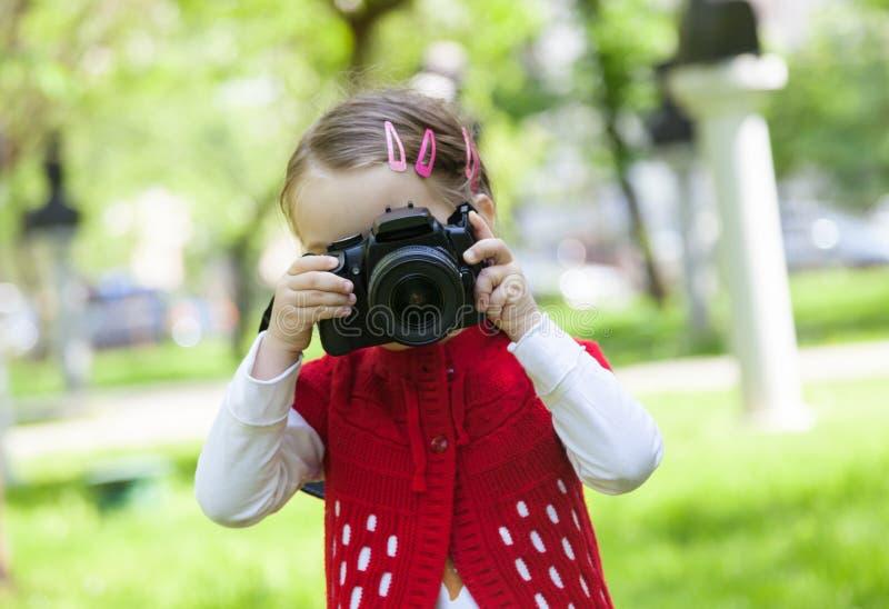 Lilla flickan, som tar, bilder med en fotokamera parkerar in royaltyfria foton
