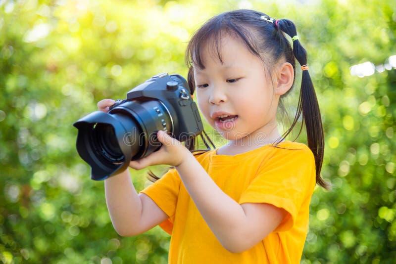 Lilla flickan som tar fotoet vid kameran parkerar in arkivbild