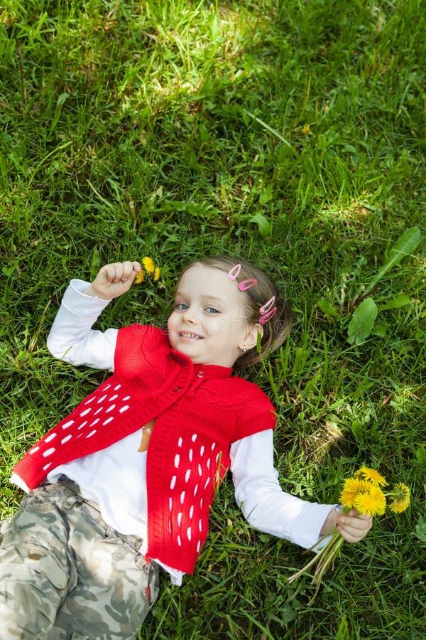 Lilla flickan som vilar på grönt gräs i vår, parkerar utomhus royaltyfri foto