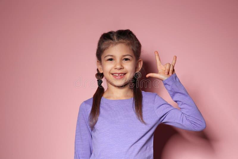 Lilla flickan som visar ÄLSKAR JAG, DIG gesten i teckenspråk på bakgrund arkivfoton