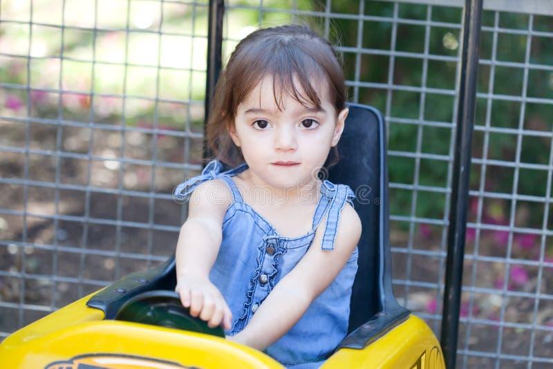 Lilla flickan spelar en chaufför royaltyfri foto