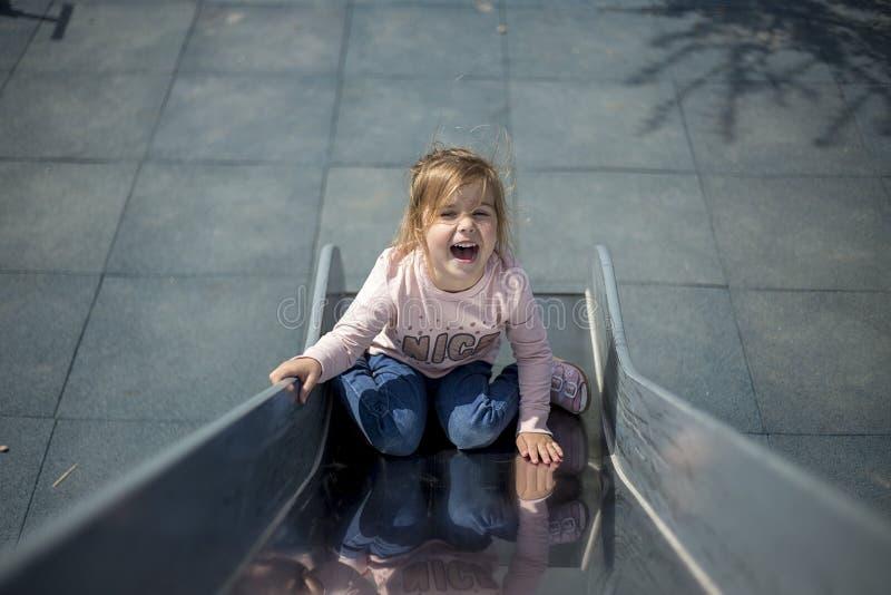 Lilla flickan spelar i lekplatsen arkivfoton